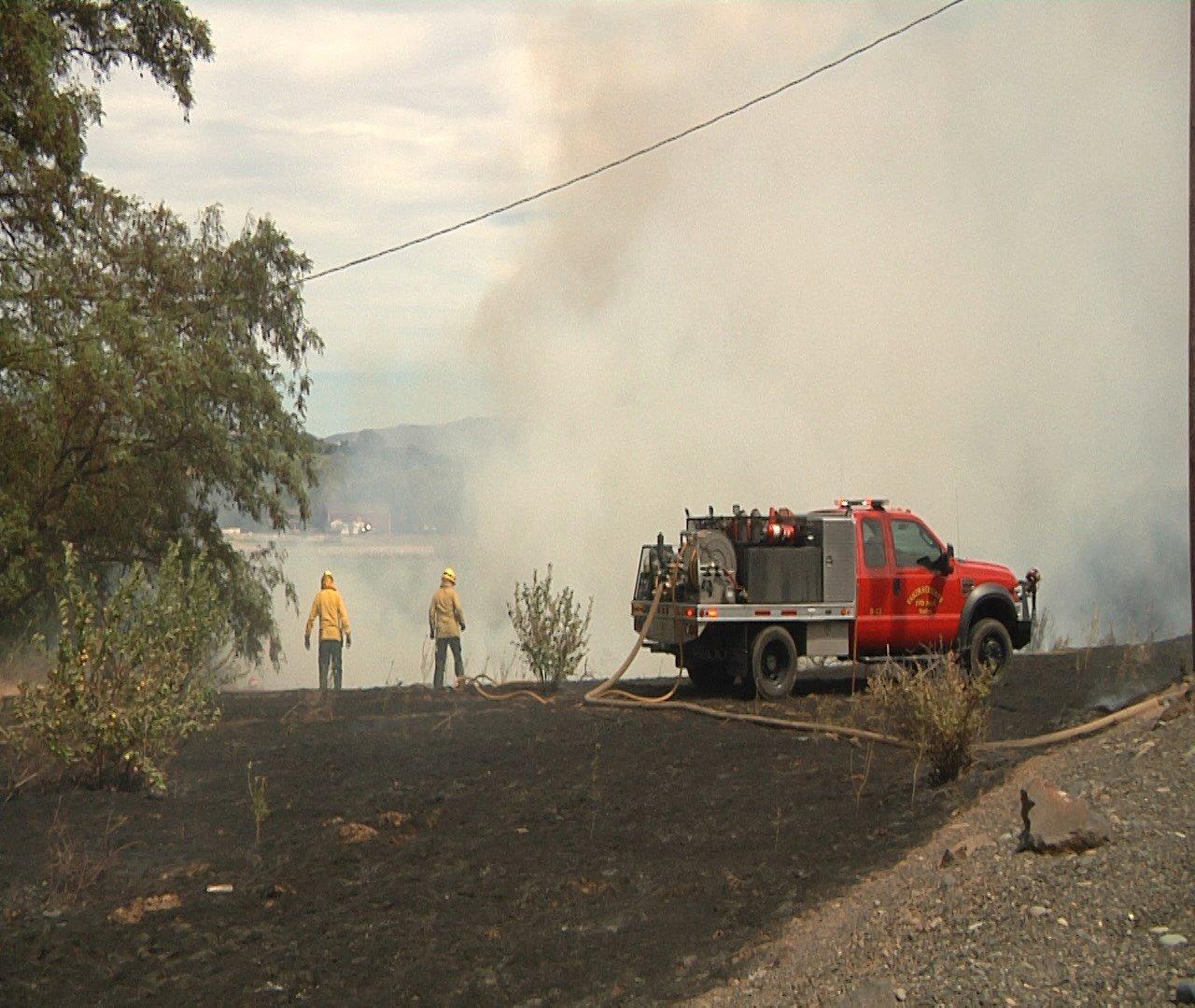 Fire crews work to mop up a brush fire.