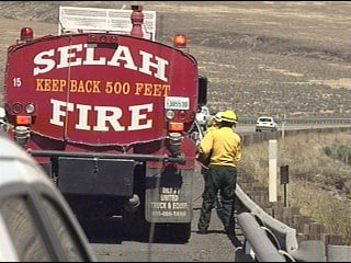 Photo of fire crews putting out brush fire along I-82 Friday