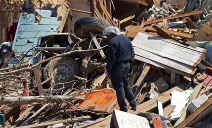 "AP Photo/Dave Martin ""Loretta Williams looks over the remains of her mother's tornado ravaged home in Tuscaloosa, Ala. Her mother, two sons and daughter survived by hiding in a closet."""