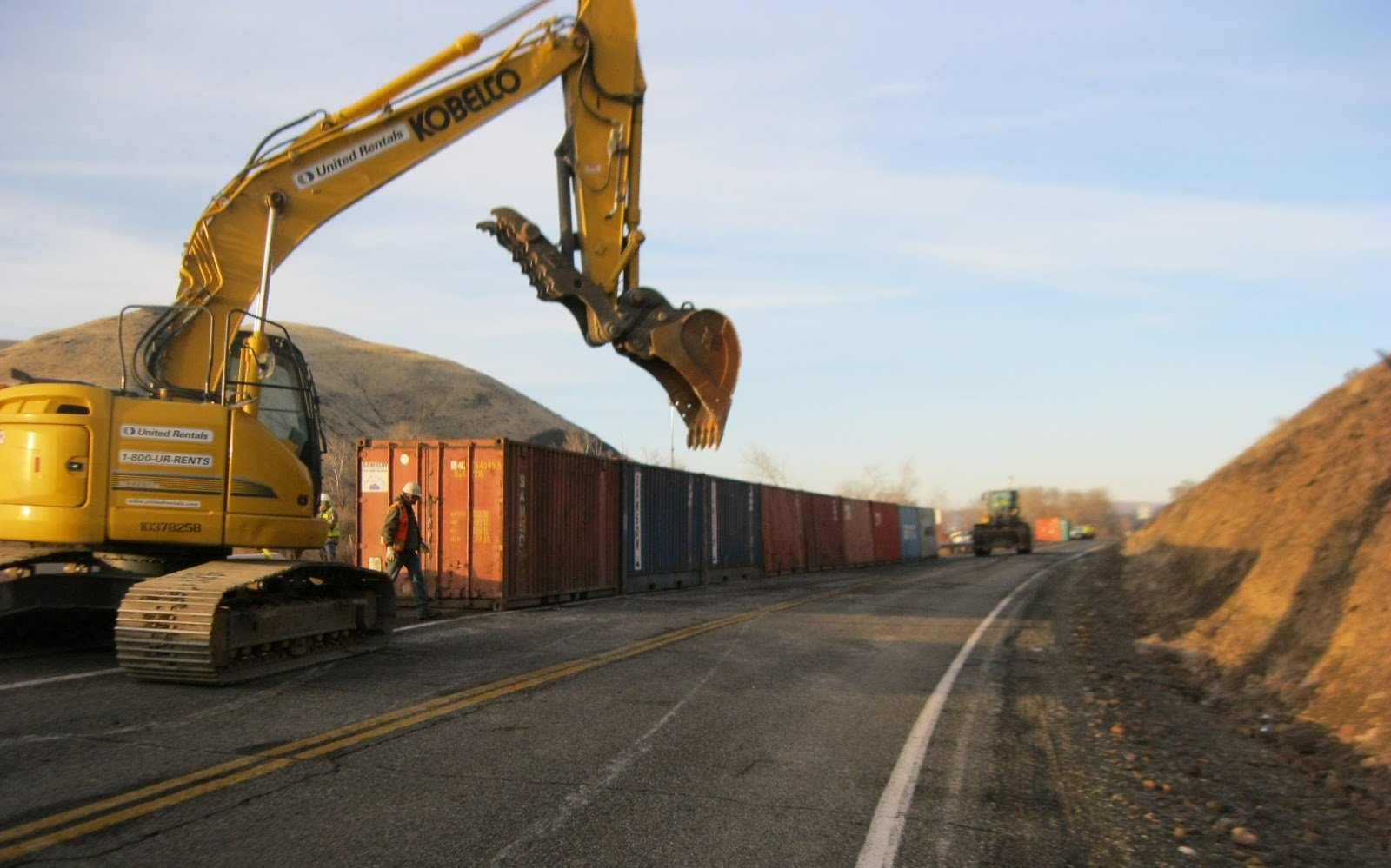 Contractor crews install freight containers along Thorp Road as a precautionary measure to keep rocks from hitting I-82 east of Yakima.