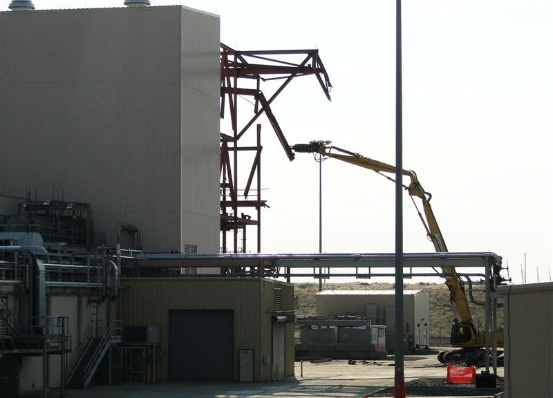 "A demolition excavator removes ""red iron"" from the structure supporting pollution abatement system equipment."