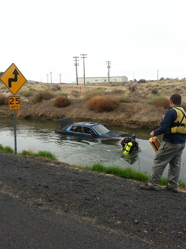© Divers with the Columbia Basin Dive Rescue work to remove a car from the water, near Canal Drive and Pederson Road in West Richland, Wednesday morning.