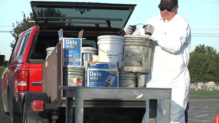 Workers unload household hazardous waste at fairgrounds. Collection continues Saturday.