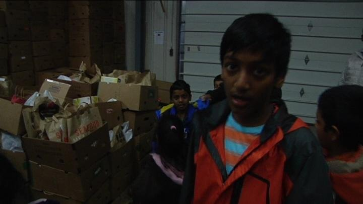 Viknesh Kasthuri Stands in Front of the Trick-or-Food Donations.