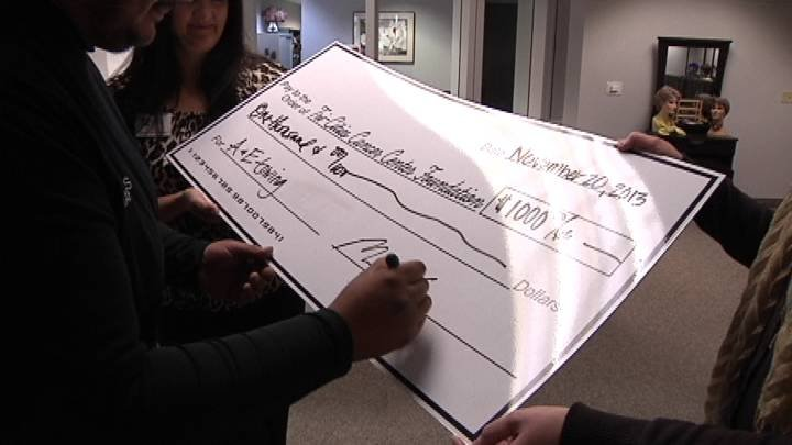 Marcos Escobar, owner of A&E Towing, cuts a check to the Tri Cities Cancer Center Foundation.