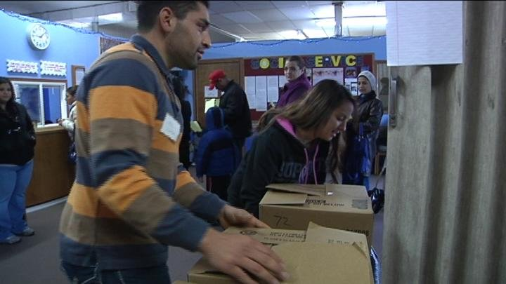 Ray, a volunteer at the Salvation Army, hands out boxes of food to hundreds of needy families.
