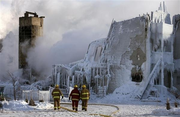 Courtesy: Mathieu Belanger -- Firefighters walk past the Residence du Havre after a fire in L'Isle Verte, Quebec, on Thursday.