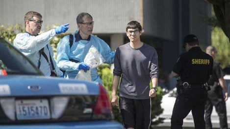 Jon Meis, the Seattle Pacific University building monitor who tackled the gunman, is escorted from Otto Miller Hall Thursday. Courtesy: The Seattle Times