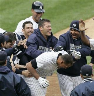 AP - Alex Rodriguez is greeted at home plate by teammates after hitting a game-winning grand slam in the ninth inning on April 7.