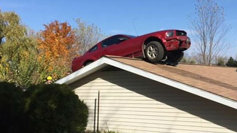 Owner hears 'kaboom,' finds car on roof of Michigan home