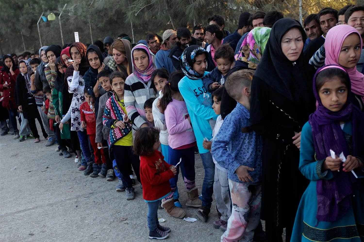 Migrants wait in line to get food in a reception center on the Greek island of Lesbos on Nov. 16, 2015 after crossing the Aegean Sea from Turkey. ORESTIS PANAGIOTOU / EPA